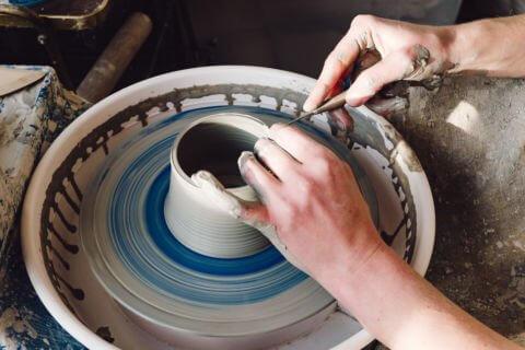 Zwei Hände formen auf einer Drehscheibe mit Ton ein Töpferei Produkt
